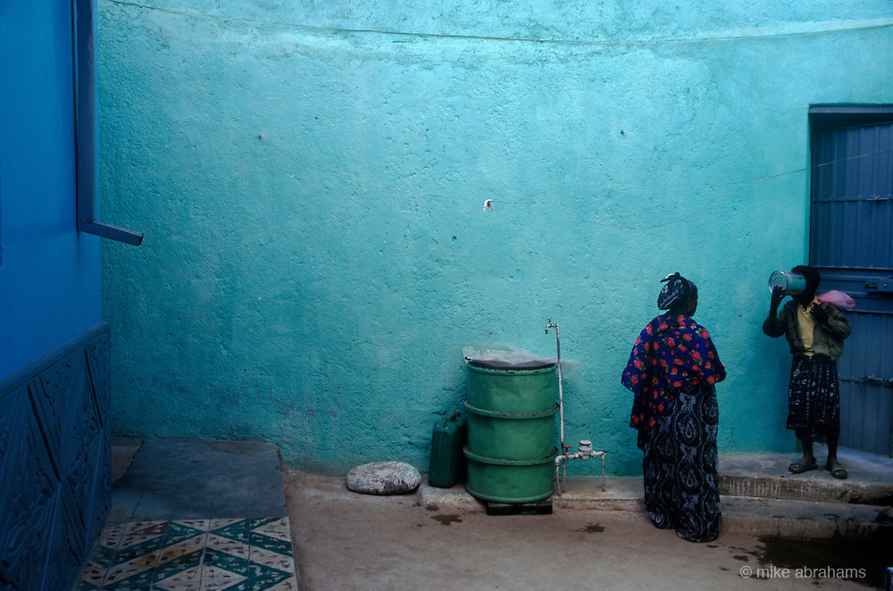 Boy drinking fro a tin can in front of A turquoise wall in the ancient walled city of Harar,  Ethiopia