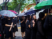 26 OCTOBER 2017 - BANGKOK, THAILAND:  People stand under umbrellas during a late afternoon monsoon storm while they wait to pay respects to the king during the funeral ceremony for Bhumibol Adulyadej, the Late King of Thailand. The king died on 13 October 2016 and was cremated 26 October 2017, after a mourning period of just over one year. The revered monarch was the longest reigning king in Thai history and is credited with guiding Thailand through the turbulent latter half of the 20th century.       PHOTO BY JACK KURTZ