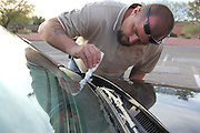 A plain clothes police officer does Vehicle Identification Number (VIN) etching at the Northwest Neighborhood Center Safety Fair in Tucson, Arizona. VIN etchings on windows makes autos less attractive to thieves.