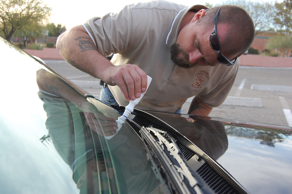 A plain clothes police officer does Vehicle Identification Number (VIN) etching at the Northwest Neighborhood Center Safety Fair in Tucson, Arizona. VIN etchings on windows makes autos less attractive to thieves. Event photography by Martha Retallick.
