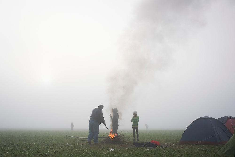 Refugees burn excess clothing to stay warm at a refugee camp on the Macedonian (FYROM) border on the morning of March 8, 2016 in Idomeni, Greece.
