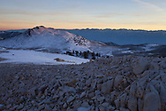 The desolate moonscape of the White Mountains glows in the dim twilight, as the sun sets over the crest of the eastern Sierra beyond, White Mountains, CA