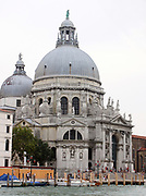 The Basilica of St Mary of Health (Santa Maria della Salute), Roman Catholic church and minor basilica located in the Dorsoduro sestiere of the Italian city of Venice. It stands on a narrow finger of land between the Grand Canal and the Bacino di San Marco making the church visible when entering the Piazza San Marco from the water. In 1630 Venice experienced an unusually devastating outbreak of the plague. As a votive offering for the city's deliverance from the pestilence, the Republic of Venice vowed to build and dedicate a church to Our Lady of Health (or of Deliverance, Italian: Salute). The church was designed in the then fashionable baroque style by Baldassare Longhena, who studied under the architect Vincenzo Scamozzi. Construction began in 1631.