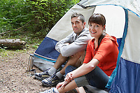 Couple sitting in tent entrance smiling portrait