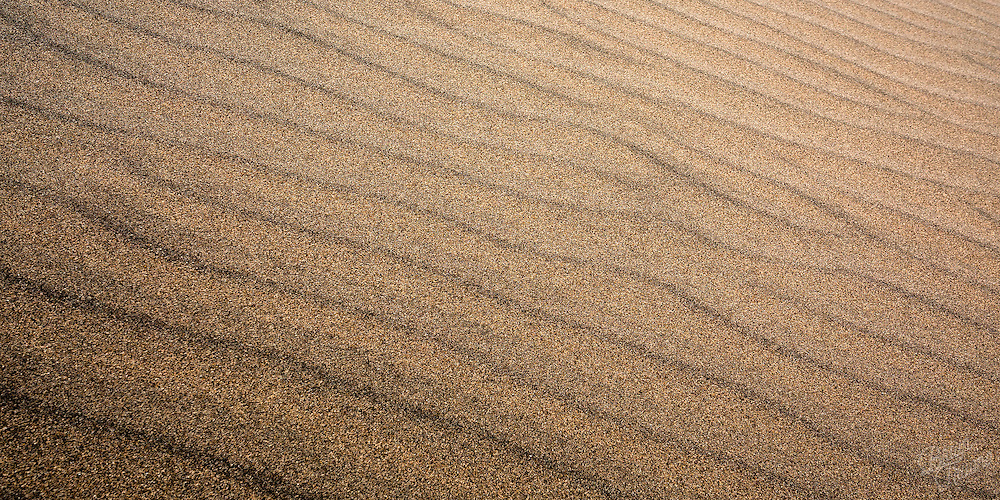 Fine particles of sand blown into patterns.