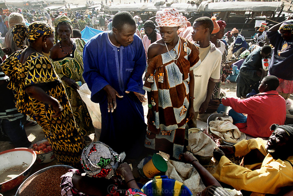 Grain trader Soumana Natomo (in blue) negotiates prices during market day in Kouakourou, Mali. Africa, Work. From coverage of revisit to Material World Project family in Mali, 2001.