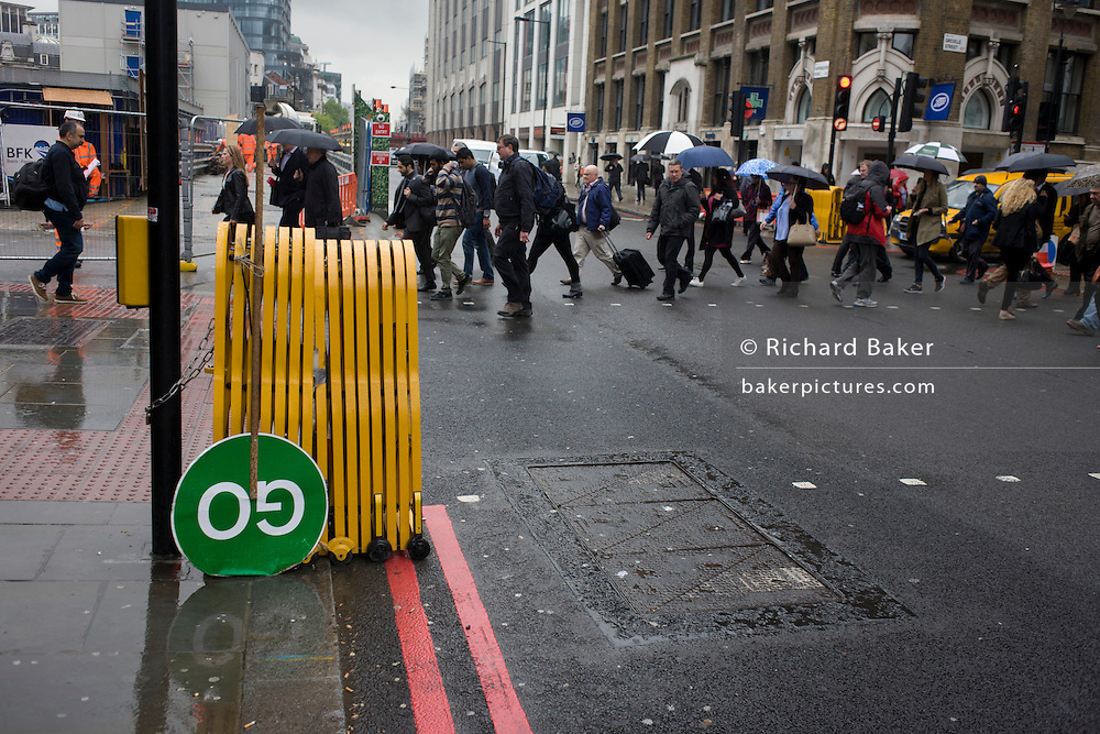 Commuters cross road and upside down GO construction traffic sign in a busy London rush-hour street.
