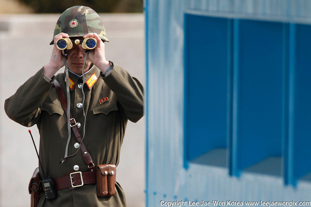 A North Korean soldier looks to the South as he patrols at the truce village of Panmunjom in the demilitarised zone separating the North from South Korea in Paju, about 55 km (34 miles) north of Seoul March 19, 2013. /Lee Jae-Won