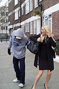 A youth in a hoodie, mugging a young woman, snatching her bag, UK 2008
