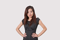 Portrait of beautiful young businesswoman with hands on hips over white background