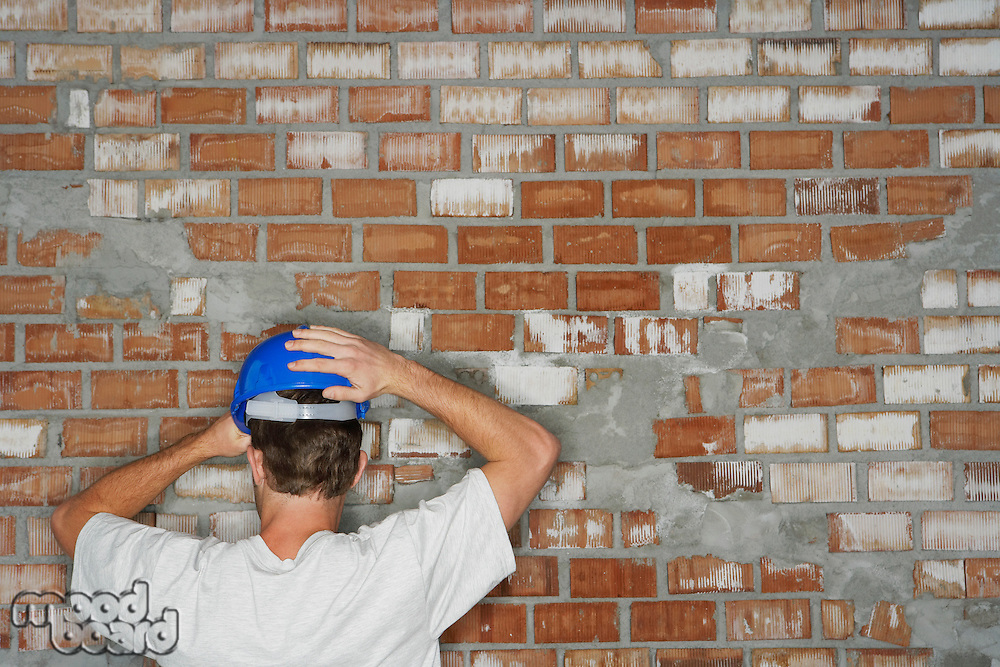 Young construction worker by brick wall back view