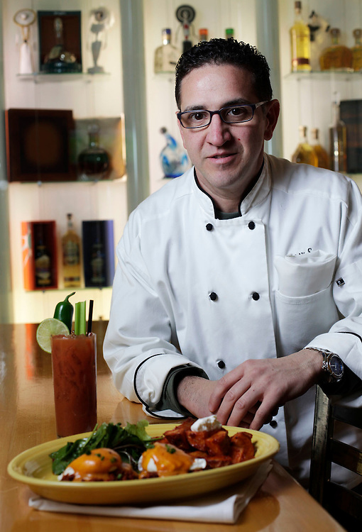 (122611, Boston, MA)- Chris Damian, chef/owner at Papa Gayo, 283 Summer Street, Boston, shows off Mexican Eggs Benedict with chorizo, chili-spiked Hollandaise sauce and chipotle potatoes along with a Bloody Maria on Monday....Herald Photo by Brooks Canaday.