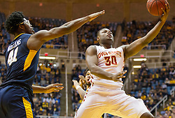Feb 22, 2016; Morgantown, WV, USA; Iowa State Cyclones guard Deonte Burton (30) shoots in the lane while defended by West Virginia Mountaineers forward Devin Williams (41) during the first half at the WVU Coliseum. Mandatory Credit: Ben Queen-USA TODAY Sports