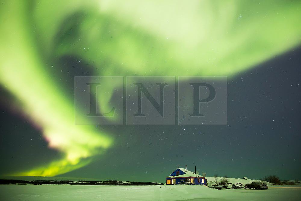 © Licensed to London News Pictures. 10/12/2018. Yellowknife, Canada. The aurora borealis is seen over the frozen, and snow covered, Slave Lake outside the city of Yellowknife in Canada's Northwest Territories. Also known as the Northern Lights, auroras occur when electrons and protons collide with gases in the Earth's upper atmosphere, causing tiny flashes that appear as light. Photo credit: Matt Cetti-Roberts/LNP