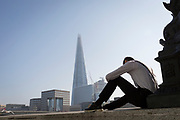 An office worker wearing braces in the City of London - the capital's financial district - enjoys late summer temperatures on Hanseatic Walk that overlooks the Shard skyscraper and London Bridge on the Thames river, on 10th October 2018, in London, England.
