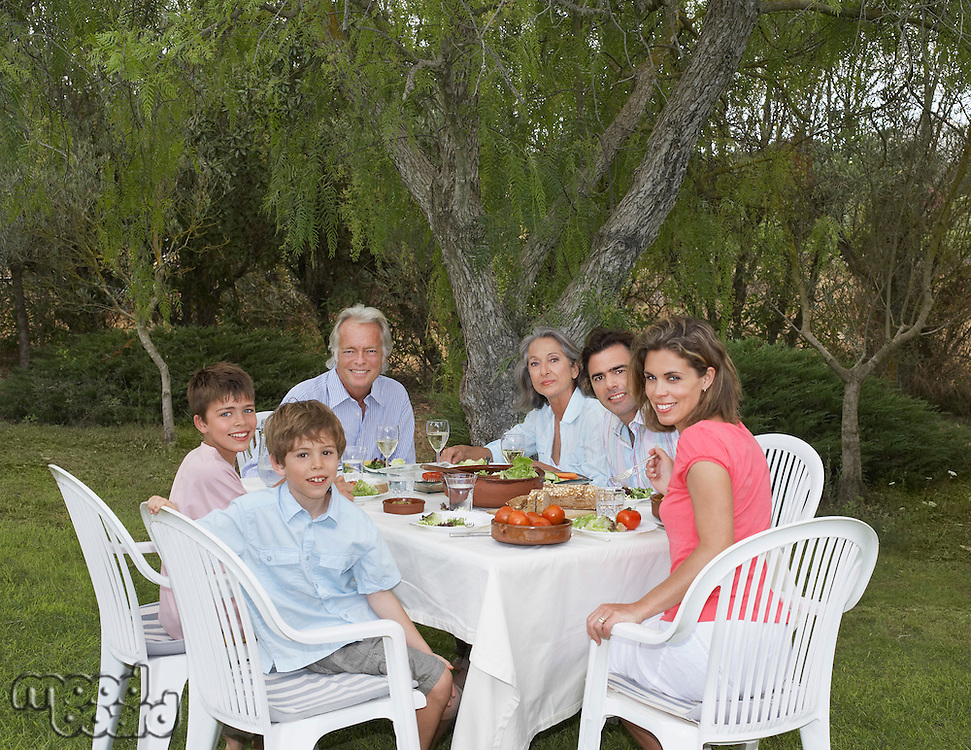 Portrait of three-generation family including children (6-11) at sitting garden table