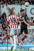 Adam Lallana wins a header against Jonathan Walters during the Barclays Premier League match between Stoke City and Liverpool at the Britannia Stadium, Stoke-on-Trent, England on 9 August 2015. Photo by Alan Franklin.