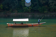 Tourists sightseeing on a small boat on the Oi River in the Arashiyama Region outside, Kyoto, Japan