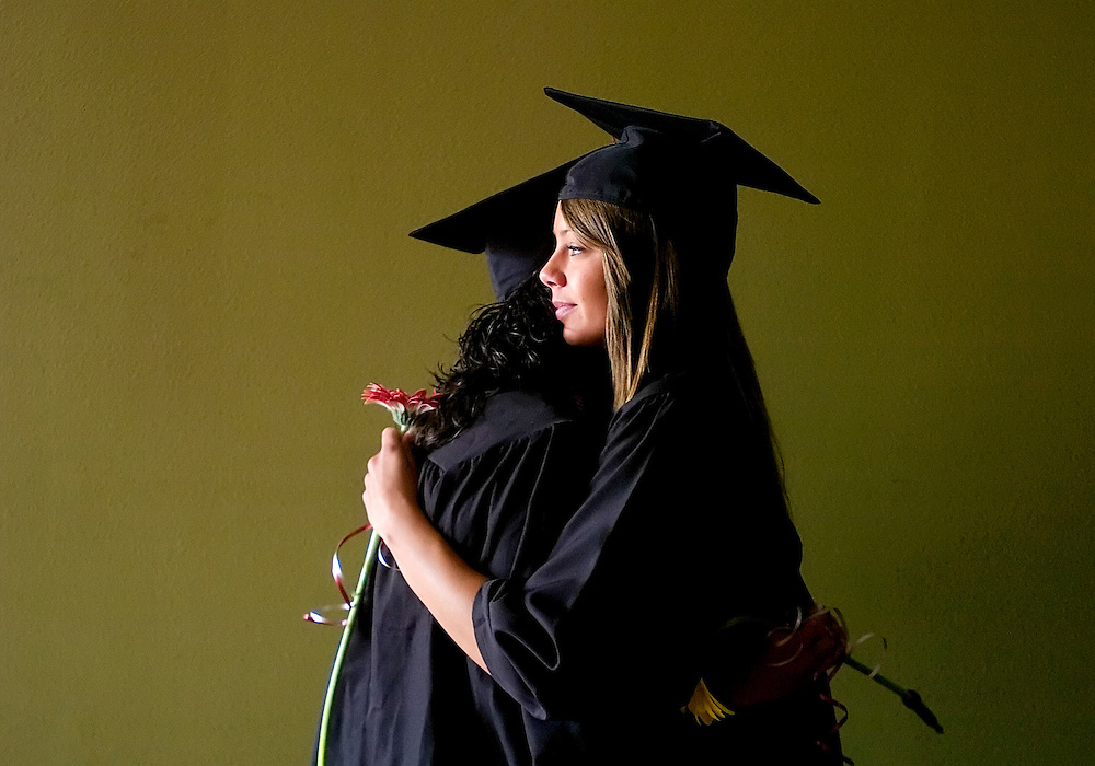 052408      Brian Leddy.Rehoboth High School senior Elizabeth Kempkes gives fellow graduate Tiffany a hug during Saturday's graduation ceremonies at the school. Thirty-five students received diplomas.