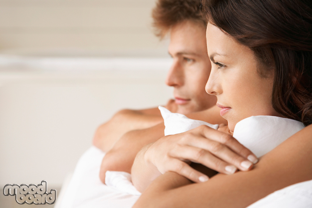 Couple lying on stomachs in bed head and shoulders profile