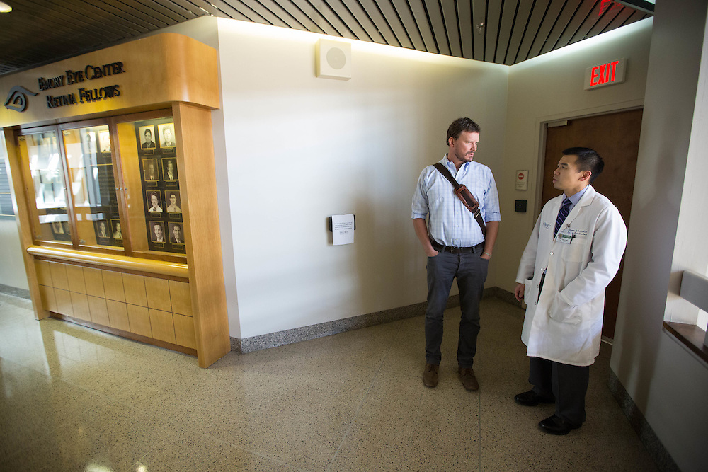Dr. Steven Yeh (right), an ophthalmologist, talks with Dr. Ian Crozier at the Emory Eye Center following an eye exam on Friday, March 27, 2015 in Atlanta, Ga. Crozier survived Ebola and now suffers from some strange side effects because of the disease. Kevin Liles for The New York Times