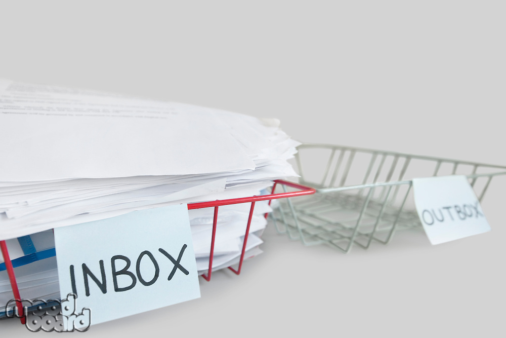 Inbox and outbox trays in an office over white background