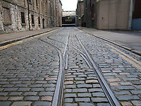 Original Cobblestone streets outside the Guinness Storehouse brewery in Dublin Ireland with old tram lines