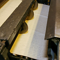 Streit's Matzoh, NYC. Matzoh dough is rolled along a conveyor belt through a machine which cuts it into squares, gives the matzoh its distinctive ridges and then sends it into the oven.