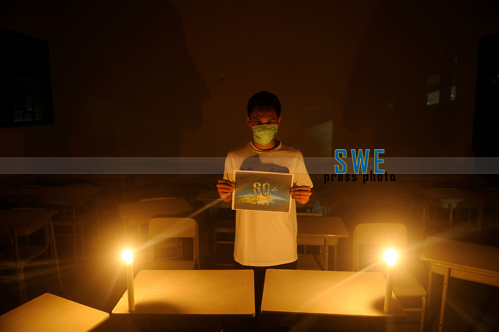 Medan, Indonesia, March 28, 2020: One of three Indonesian people, Fridus Butarbutar seen using masks and hold posters under the candle lighting in the small campaign action to welcoming Earth Hour moment to resting the earth from the electrical energy used and avoid the harmfull effects of climate changes that trigger the emergence of Corona Virus Disease 19, Photo taken in journalism campus of STIKP in Medan, North Sumatra province, Indonesia on March 28, 2020.
