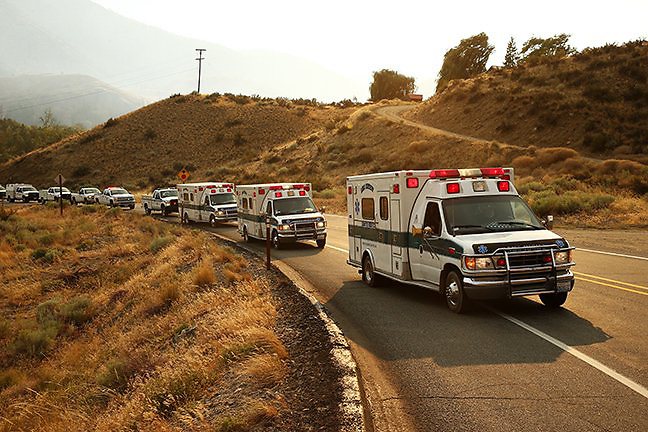 Ambulances carrying the bodies of three fallen firefighters travel out of Twisp to Omak, Washington during a procession Thursday, Aug. 20, 2015.<br />