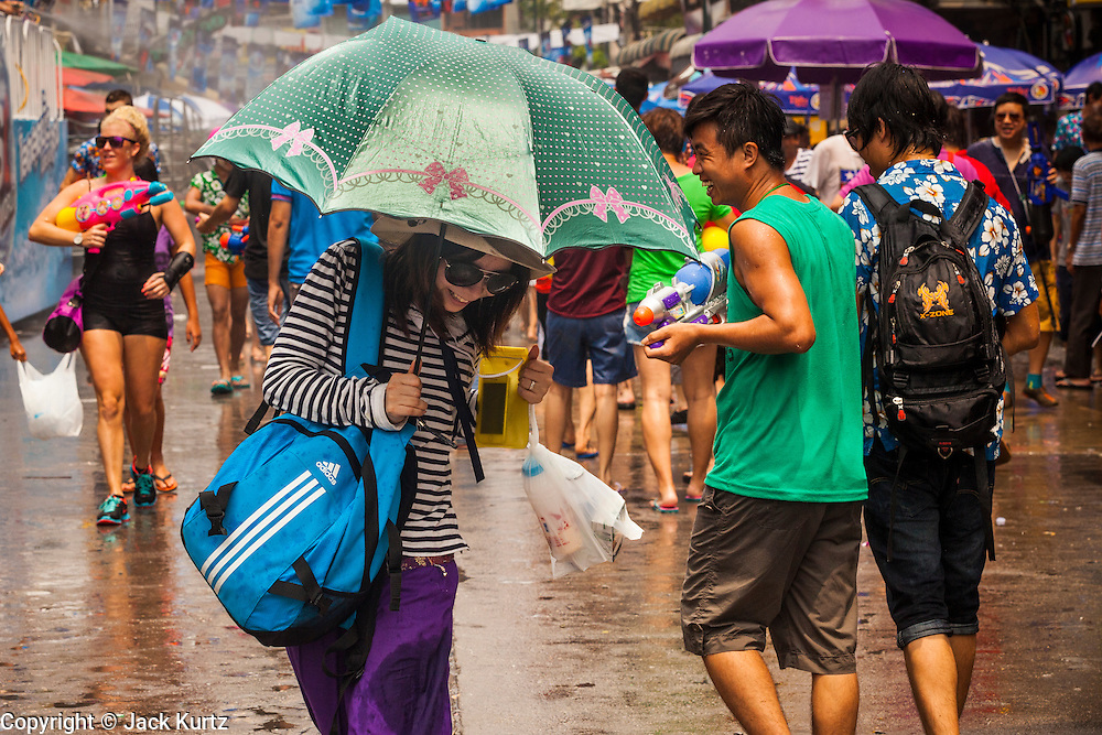 13 APRIL 2014 - BANGKOK, THAILAND: A tourist with an umbrella walks through water fights on Khao San Road, Bangkok's backpacker district, on the first day of Songkran. Songkran is celebrated in Thailand as the traditional New Year's Day from 13 to 16 April. Songkran is in the hottest time of the year in Thailand, at the end of the dry season and provides an excuse for people to cool off in friendly water fights that take place throughout the country. Songkran has been a national holiday since 1940, when Thailand moved the first day of the year to January 1.    PHOTO BY JACK KURTZ