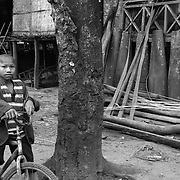"""A young boy on his bicycle outside a house lined with cluster bomb casings in the """"bomb village"""" of Ban Senphen. The village is located in the Ban Phanhop valley, one of the """"chokes"""", or narrow corridors along the Ho Chi Minh Trail in Laos that were heavily bombed by American forces during the Vietnam War."""