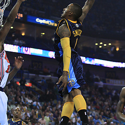 28 January 2009:  Denver Nuggets guard J.R. Smith (1) attempts a dunk as New Orleans Hornets center Hilton Armstrong (12) defends during a 94-81 win by the New Orleans Hornets over the Denver Nuggets at the New Orleans Arena in New Orleans, LA. The Hornets wore special throwback uniforms of the former ABA franchise the New Orleans Buccaneers for the game as they honored the Bucs franchise as a part of the NBA's Hardwood Classics series. .