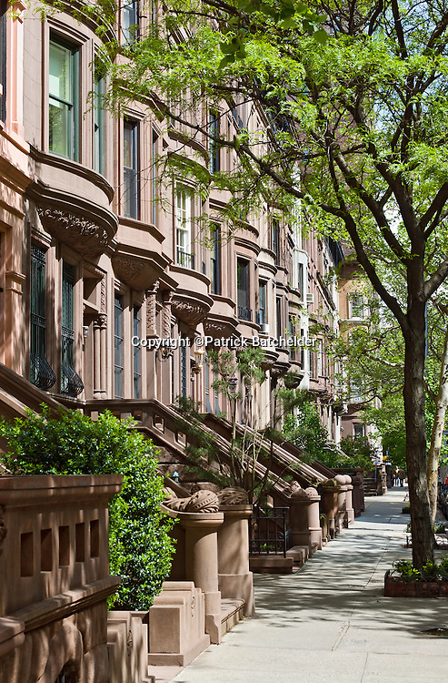 A row of beautiful brownstone apartment houses line a side street in the Upper West Side neighborhood of Manhattan, New York City.