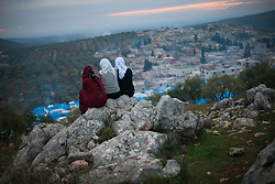 Three young girls residents of Qah's refugee camp, sitting down in a rock in the top of the hill watching the sunset in Qah town. Februaly 7th, Idlib province, Syria...Situated 7 km away from the Turkish border Qah refugee camp is one of the three refugee camps in the area -inside Syria's territory- with an estimated number of 3,200 refugees and growing by the day. Build in August 2012 by the help of Libyan al-Yosser charity and with the provision of tents, blankets etc of the Syrian National Council, Syria, February 7, 2013. Photo by Daniel Leal-Olivas / i-Images.