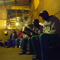 Men drink in an illegal shebeen as night falls on Imizamo Yethu shanty town, Hout Bay, Cape Town, South Africa. The work of the CPF and neighbourhood watch have seen the crime rate in Hout Bay drop 63%, but relations between the shanty town of Imizamo Yethu and Hout Bay are tense.  photo  Leonie Marinovich