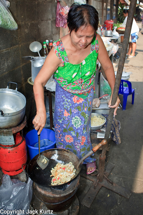 "Mar. 21, 2009 -- BANGKOK, THAILAND:  A food vendor prepares her lunch stand in a narrow alley in the Monk's Bowl Village. The Monk's Bowl Village on Soi Ban Baat in Bangkok is the only surviving one of what were originally three artisan's communities established by Thai King Rama I for the purpose of handcrafting ""baat"" the ceremonial bowls used by monks as they collect their morning alms. Most monks now use cheaper factory made bowls and the old tradition is dying out. Only six or seven families on Soi Ban Baat still make the bowls by hand. Most of the bowls are now sold to tourists who find their way to hidden alleys in old Bangkok. The small family workshops are only a part of the ""Monk's Bowl Village."" It is also a thriving residential community of narrow alleyways and sidewalks.     Photo by Jack Kurtz"