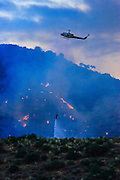 22 JUNE 2005 - CAVE CREEK, AZ:   A helicopter makes an evening water drop on the Cave Creek Complex, a large wild fire which burned northeast of Phoenix. The Cave Creek Complex fire was the third largest wildfire in the state of Arizona to date, after the Rodeo-Chediski fire and Wallow Fire. The fire started on June 21, 2005 by a lightning strike during a monsoon storm and burned 243,950 acres (987.2 km2).   PHOTO BY JACK KURTZ
