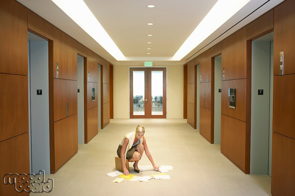 Woman picking dropped papers from floor in elevator lobby elevated view