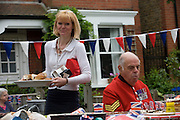 Serving the elderly at a community street party in Dulwich, south London celebrating the Diamond Jubilee of Queen Elizabeth. A few months before the Olympics come to London, a multi-cultural UK is gearing up for a weekend and summer of pomp and patriotic fervour as their monarch celebrates 60 years on the throne and across Britain, flags and Union Jack bunting adorn towns and villages.