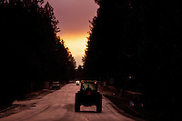 A tractor travels west on Shadduck Lane during a colorful sunset Friday, March 25, 2011 after a rain storm.