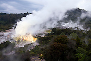 geothermal activity, hot water, steam clouds, vegetation, overview, dusk, lights, Te Puia Maori cultural center, Rotorua,  New Zealand