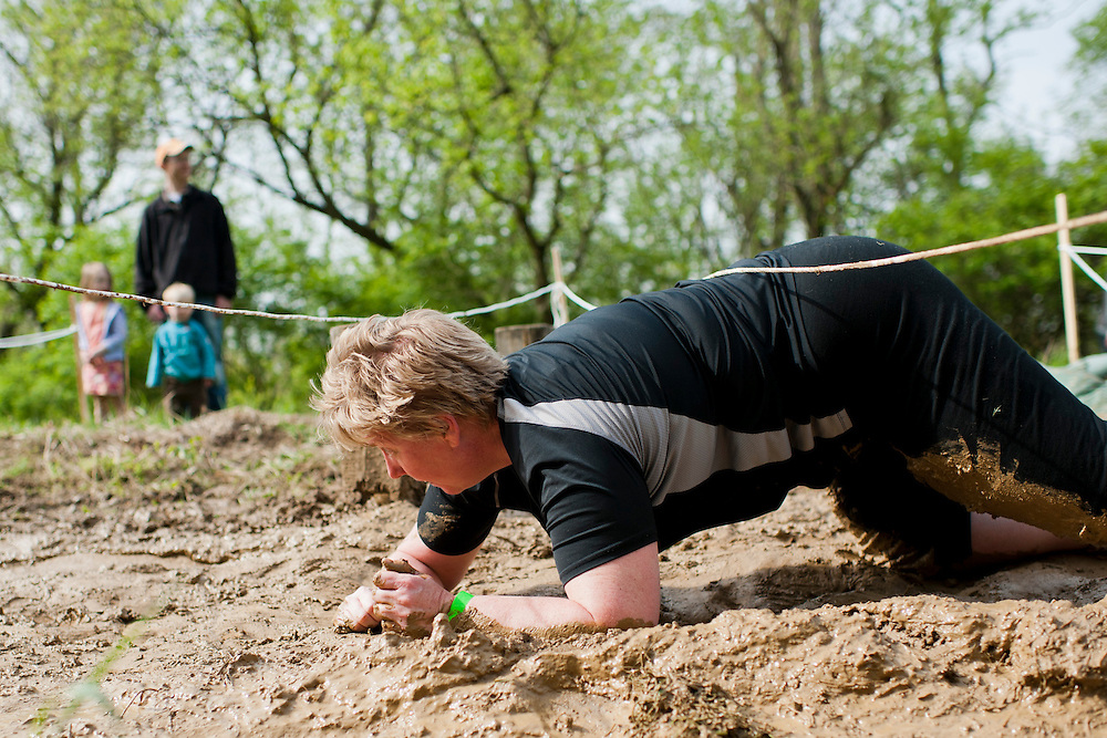 A participant crawls through the mud at the old Army ROTC training course located at the Ridges during the O'Bleness Race for a Reason Mud Run, Saturday, April 27, 2013. The course included a four-mile run up to the old Army ROTC Course at the Ridges, through the Radar Hill Trail and back to Tail Great Park across from Peden Stadium. Race for a Reason, Race 4 A Reason, Annual Events, Events, Students, Faculty & Staff