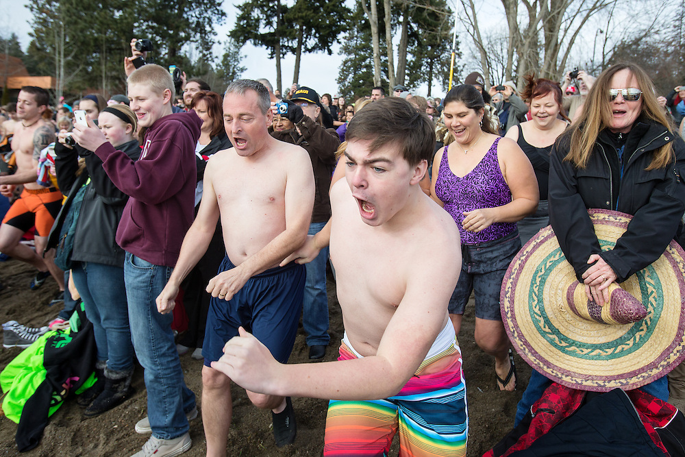 The first wave of Polar Bear plungers rushes Sanders Beach into Lake Coeur d'Alene Wednesday morning.