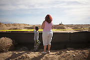 Photo by Steven St. John..Albuquerque residents Leanora Prudencio watches with her 6-year-old son Phillip Prudencioon Monday, March 2, 2009 on the southwestern outskirts of Albuquerque, N.M. at the site of a planned residential subdivision. Investigators and forensics experts are searching the crime scene where the remains of at least 13 bodies have been uncovered. The discovery has opened up cases involving missing prostitutes, some of whom vanished as much as 20 years ago.