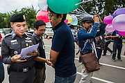"24 JUNE 2014 - BANGKOK, THAILAND: A Thai police officer (left) talks to a poet  (right) about his poem after he read it aloud at a meeting of the Monsoon Poets Society in Bangkok. Members of the ""Monsoon Poets Society"" gathered in front of the Anantasamakom Throne Hall Tuesday to pay homage to the People's Party, a Siamese (Thai) group of military and civil officers (which became a political party) that staged a bloodless coup against King Prajadhipok (Rama VII) and changed Thailand (then Siam) from an absolute monarchy to a constitutional monarchy on 24 June 1932. Since the coup against the civilian government on 22 May, the ruling junta has not allowed political gatherings. Although police read the poems, they did not arrest any of the poets or make any effort to break up the gathering.     PHOTO BY JACK KURTZ"