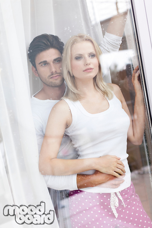 Loving young couple looking through hotel window