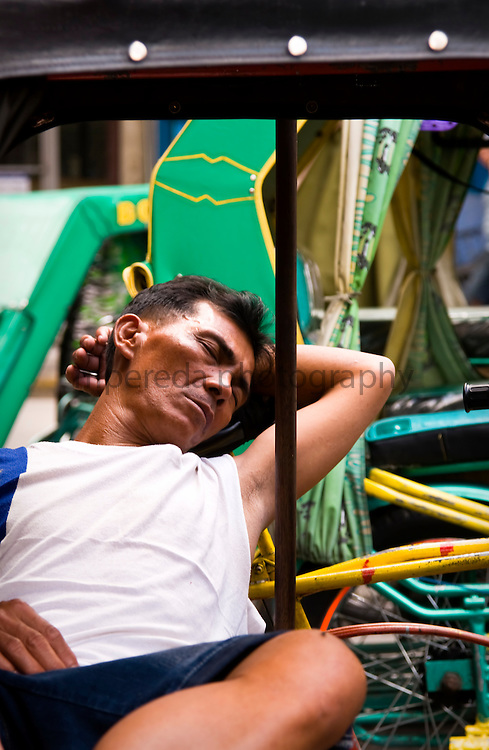 MANILA (Philippines). 2009. Tricycle´s driver sleeping in his vehicle.