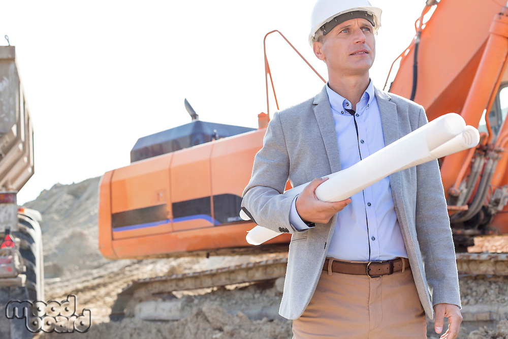 Confident architect looking away while holding blueprints at construction site