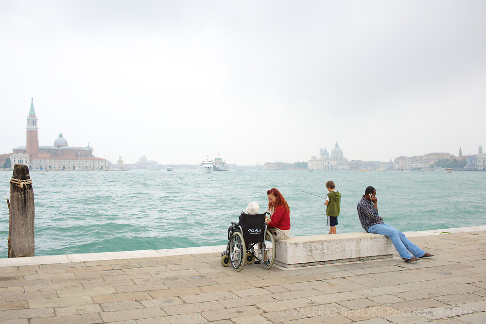 A old woman and her companion, a child fishing and an immigrant on the shore of Venice lagoon.
